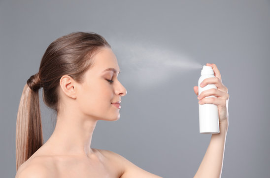 Young woman applying thermal water on face against grey background. Cosmetic product