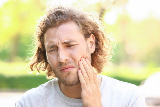 Young man suffering from toothache outdoors