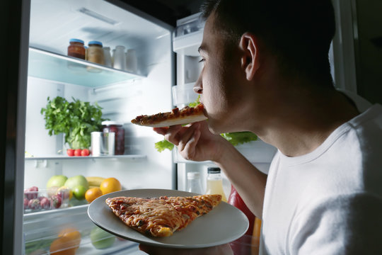 Young man eating pizza near refrigerator at night