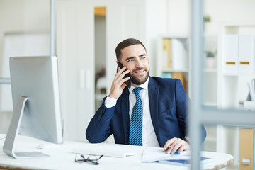Positive confident handsome young project manager with beard sitting at table and discussing plans with colleague on mobile phone