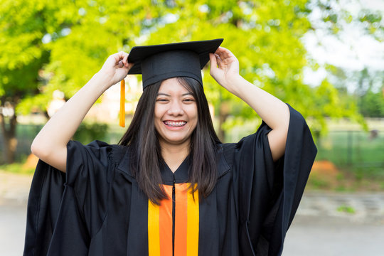 Portrait of a female university graduate wears black academic gown and hat, holds degree certificate with joyful moment after graduation the program in graduation ceremony. University graduation.