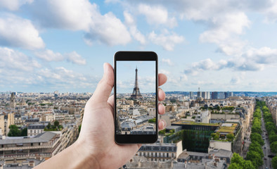 Hand taking photo of Eiffel tower, famous landmark and travel destination in Paris, France by mobile smart phone