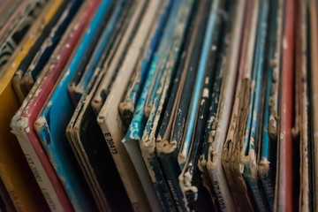 A colorful collection of  antique vinyl records in cases stacked up against each other. Antique collectors, millennial trends, old music technology concepts.