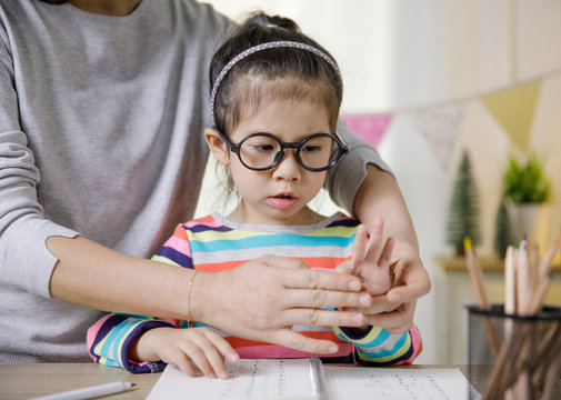 Mom teaching her daughter to writing in the book on the table, Educational concept for school