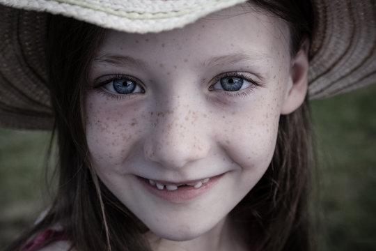 Ein junges Mädchen mit Strohhut freut sich über den Sommer, endlich Ferien