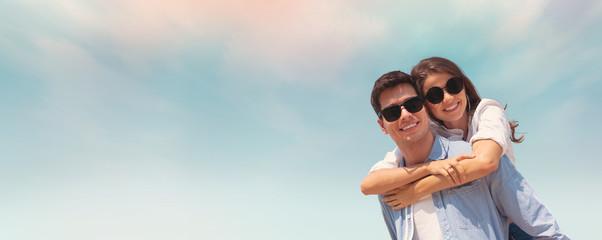 couple wear sunglasses having fun on blue sky and the beach. Wall mural