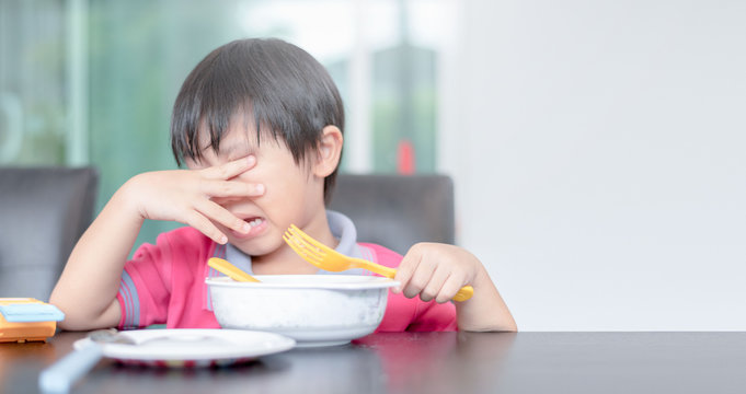 asian child boy eating boring food in morning