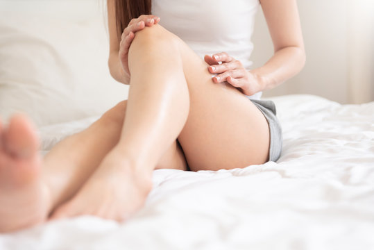 Asian female applying body lotion on her legs.