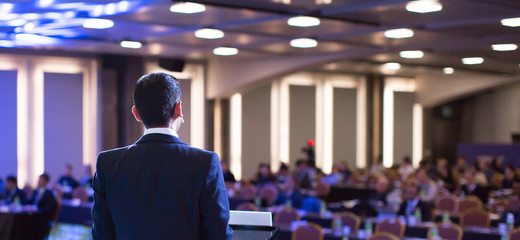 Speaker giving a talk at a corporate business conference. Audience in hall with presenter in front...