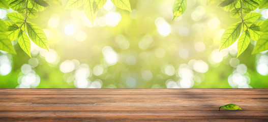 wooden table with natural view of green leaves in garden, ray of sunlight though tree leaves in...