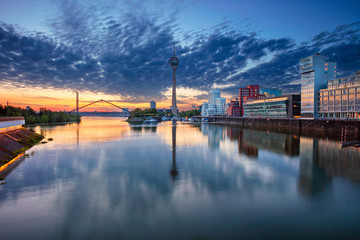 Fototapete - Düsseldorf, Germany. Cityscape image of Düsseldorf, Germany with the Media Harbour and reflection of the city in the Rhine river, during sunrise.