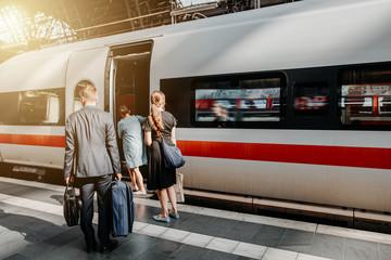 Reisende Menschen zur Rush Hour am Bahnhof mit Gepäck