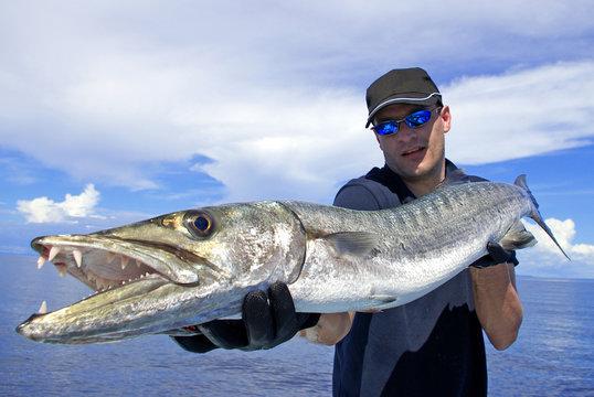 Deep sea fishing, catch of fish, big game fishing, fisherman holding a giant barracuda