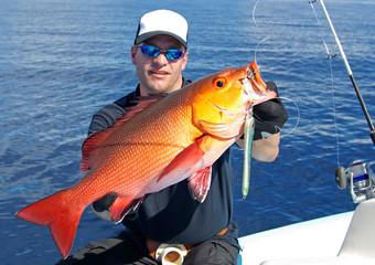 fisherman holding a big red snapper fish, deep sea fishing, lure fishing, big game fishing. Catch of fish