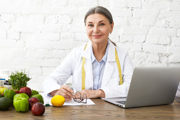 Indoor shot of positive smiling Caucasian female nutritionist in her sixties working online,...