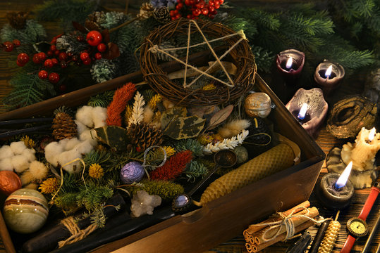 Esotеric and wicca still life with box of gifts, pentagram, candles and herbs on witch table.