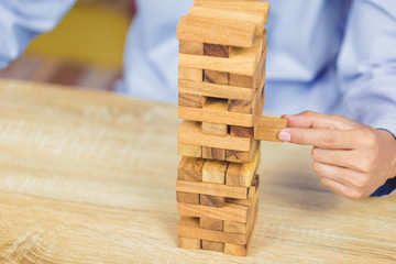 Hand of businessman pulling out or placing wood block on the tower, plan and strategy in business.