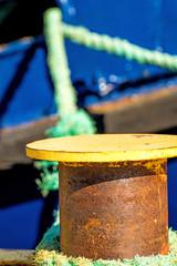 bollard with mooring line and blue ship hull