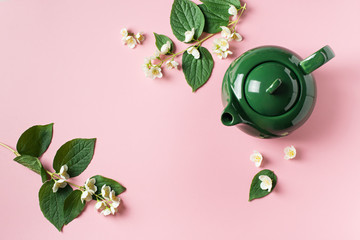 Jasmine tea with teapot, flowers and leaves on pink background Wall mural