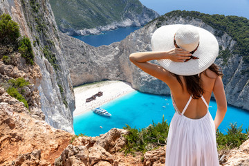 Touristin in weißem Sommerkleid steht auf einer Klippe und genießt die Aussicht auf den...
