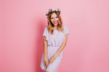 Wall Mural - Lightly-tanned girl in trendy flower wreath laughing during photoshoot. Portrait of smiling blonde woman in summer dress isolated on pink background.