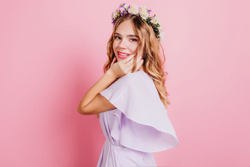 Wall Mural - Beautiful blonde woman wears stylish wreath posing in studio with pink interior. Portrait of gorgeous caucasian girl with floral accessory.