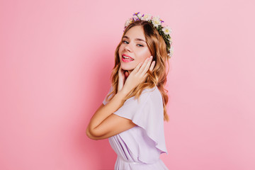 Wall Mural - Graceful white lady touching her face and smiling. Indoor portrait of magnificent blonde girl in flower wreath standing on pink background.