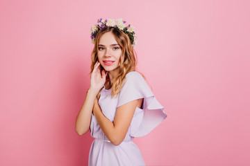 Wall Mural - Shy girl in romantic summer outfit posing on pink background. Indoor portrait of spectacular woman with blonde shiny hair looking away with serious face expression.