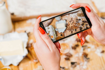 Gingerbread biscuit recipe. Lady using smartphone to take picture of pastry ingredients.