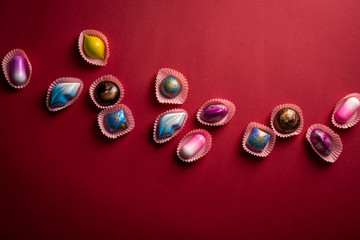 Modern colorful bonbons on red paper