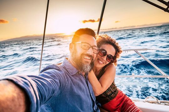 Happy and cheerful people enjoying the travel and trip on a sail boat with ocean and sunset sunlight in background - traveler lifestyle for adult man and woman smiling doing a selfie picture