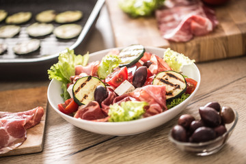 Fresh lettuce salad with grilled zucchini coppa di parma ham feta cheese olives tomatoes and olive oil