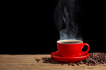hot coffee in red cup on old wooden table with black wall background.