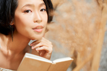 Portrait of attractive young Vietnamese woman with flawless sking holding small book looking at camera