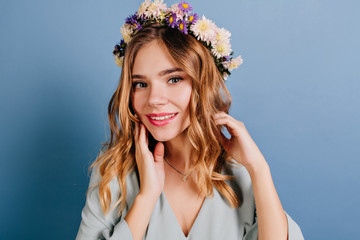 Wall Mural - Spectacular lady with pink lips and shiny hair posing on dark background. Adorable girl in flower wreath standing near blue wall.