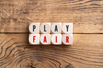 PLAY FAIR spelled with red and black letters on eight small wood blocks over rustic wooden background