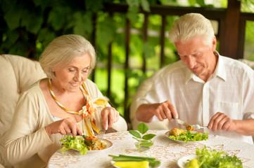 Portrait of happy senior couple having diner