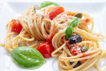 imagen fresca y luminosa de pasta con tomates cherrys, aceitunas y albahaca.