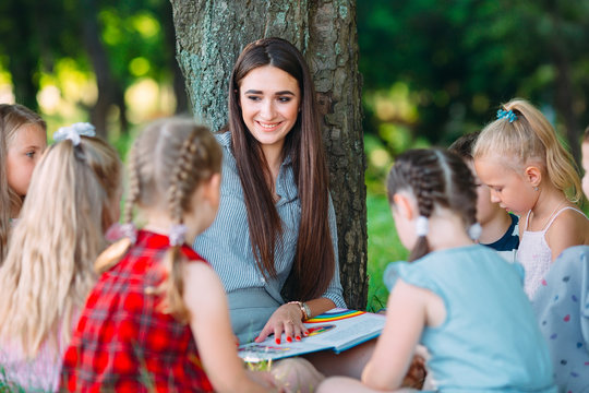 Children and education, young woman at work as educator reading book to boys and girls in park.