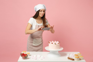 Chef cook confectioner or baker in apron white t-shirt, toque chefs hat cooking at table photographing cake for her blog isolated on pink pastel background in studio. Mock up copy space food concept.