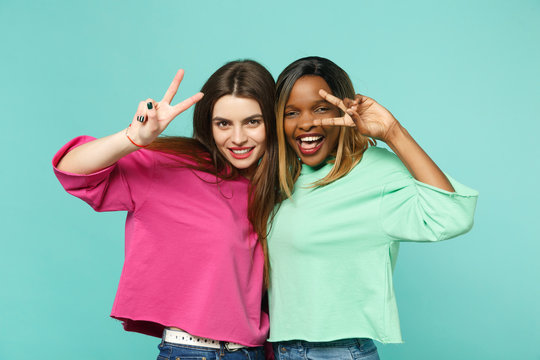 Two young women friends european, african american in pink green clothes showing victory sign isolated on blue turquoise wall background, studio portrait. People lifestyle concept. Mock up copy space.