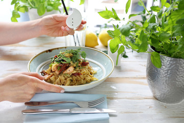 Spaghetti with salmon and sun-dried tomatoes. The woman eats a tasty dish