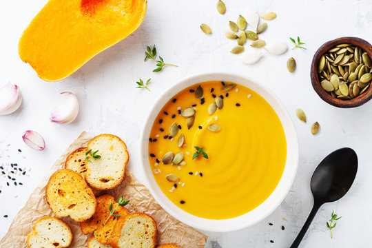 Autumn pumpkin cream soup in bowl served with seeds and crouton on white stone table top view.