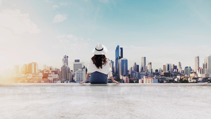 Wall Mural - Traveling in Bangkok city, Thailand. Young traveler in white hat and cloth looking at Bangkok city view from roof top in sunrise