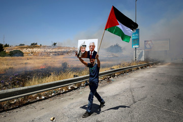 Demonstrator holds a Palestinian flag and a picture of late Palestinian leader Arafat and President Abbas during a protest in the Israeli-occupied West Bank