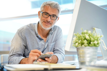 Casual mature businessman working on cellphone in modern office