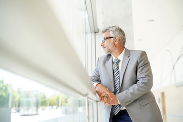Mature businessman looking out window in modern office