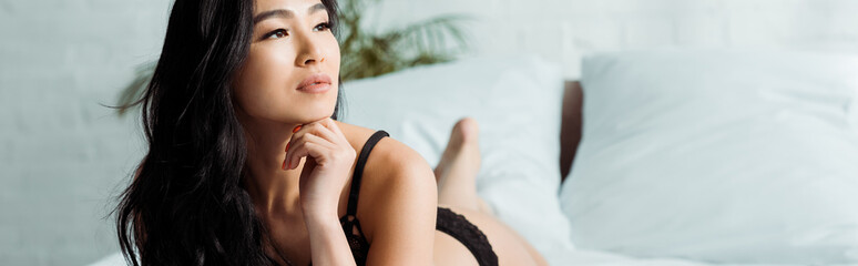 panoramic shot of pretty brunette thai woman lying on bed in black lingerie