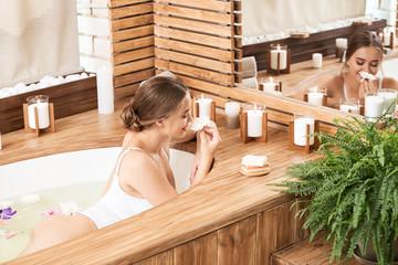 Beautiful young woman taking bath in spa salon