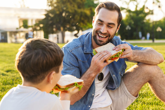 Happy young father having a picnic with his little son